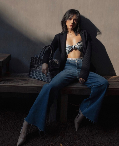 Khánh Linh chọn bra thiết kế bằng khăn quấn để tạo điểm nhấn cho set đồ gồm áo blazer mùa hè, quần jeans ống loe và túi tote của Dior.