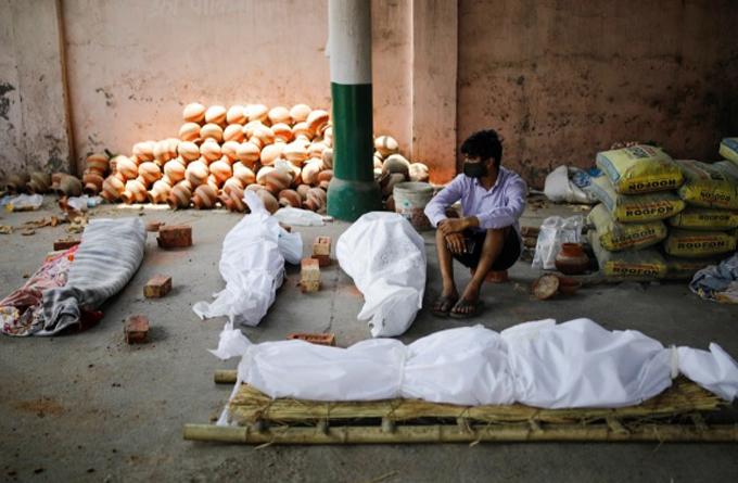 Người đàn ông Ấn Độ ngồi giữa 4 xác chết Covid-19 khi bệnh viện và các lò hỏa táng đều quá tải.