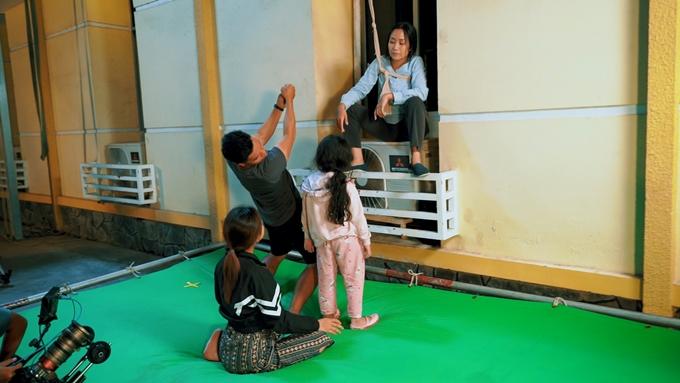 Cascadeur hướng dẫn bé Bảo Thi và Ốc Thanh Vân trong cảnh quay đu dây từ tòa nhà.