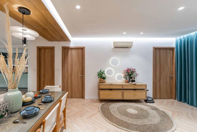 Ở mảng tường giữa hai căn phòng có tủ gỗ gắn tường để lưu trữ đồ đạc. Các hình tròn gắn tường có thêm đèn led để tạo điểm nhấn, giúp không gian sang trọng.