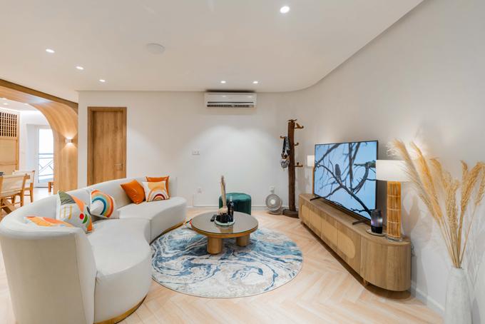 Căn hộ được thiết kế theo phong cách hiện đại, nguyên vật liệu chính cho nội thất là gỗ. Tông màu chủ đạo là màu nâu gỗ và trắng, kết hợp với các sắc xanh khác nhau ở mỗi không gian, các đường cong mềm mại cùng hệ thống đèn led bổ trợ để tạo điểm nhấn, tạo nên tổng thể tinh tế và sang trọng. Phòng khách được thiết kế đơn giản với những món đồ gọn gàng, đủ không gian để các thành viên có thể quây quần cùng nhau. Điểm nhấn cho phòng khách chính là những chiếc gối tựa màu sắc và tấm thảm màu xanh trắng loang màu tự nhiên.
