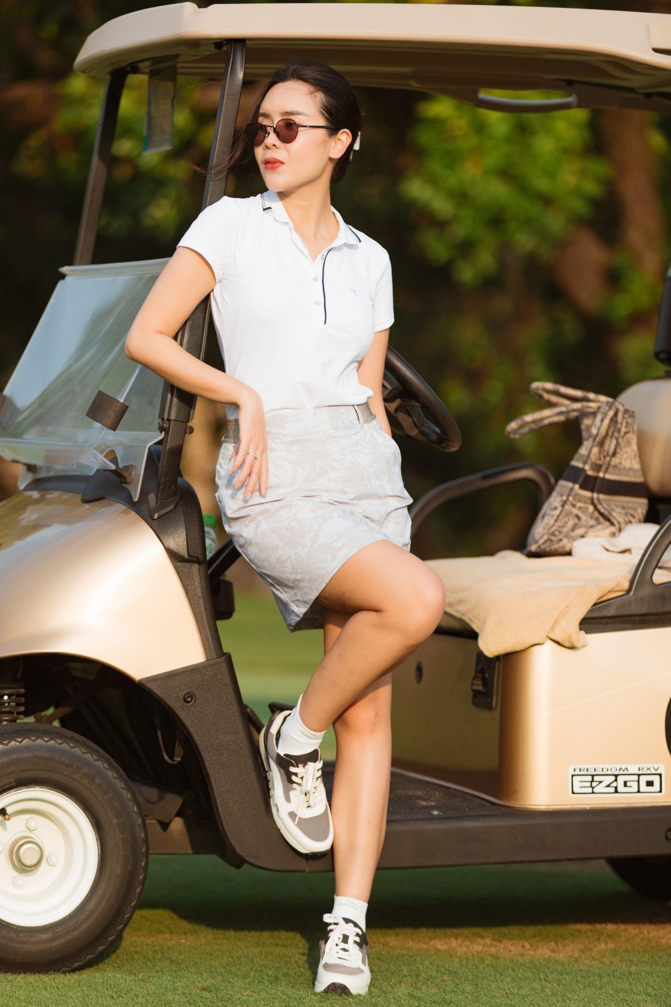 Lưu Hương Giang diện đồ ton sur ton, áo polo trắng cùng chân váy ngắn, tăng vẻ sành điệu với kính râm.