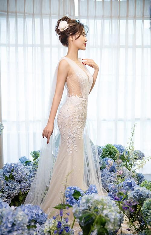 NTK Nguyễn Thanh sử dụng vải voan để tạo tà phụ, kéo dài từ cầu vai tới gót chân, tạo sự thanh thoát cho váy.