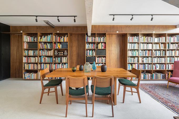 Để ngăn cách khu vực riêng tư của căn hộ với các khu vực sinh hoạt chung, tủ sách bằng gỗ đóng vai trò chia không gian. Giữa các hốc đựng sách bố trí các cửa ẩn để đi vào phòng ngủ của cặp vợ chồng, phòng con gái và khu vệ sinh cho khách.