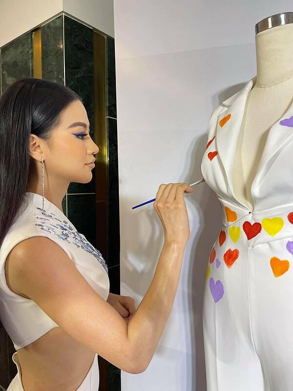 Hoa hậu Trái đất 2018 Phương Khánh dành thời gian tô điểm trang phục cho đàn em. Từng dự thi quốc tế, cô hiểu rõ áp lực nên khuyên Khánh Vân luôn giữ vững tinh thần suốt hành trình.