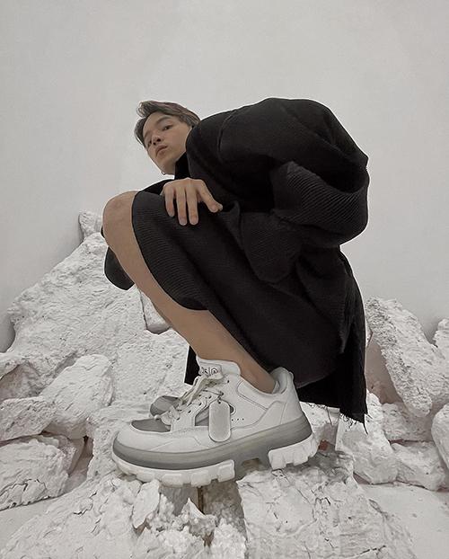 Stylist Kelbin Lei khéo tạo dáng để khoe rõ nét phom dáng kiểu giày đế thô. Anh chọn trang phục màu tương phản để thể hiện đúng phong cách mình ưa chuộng.