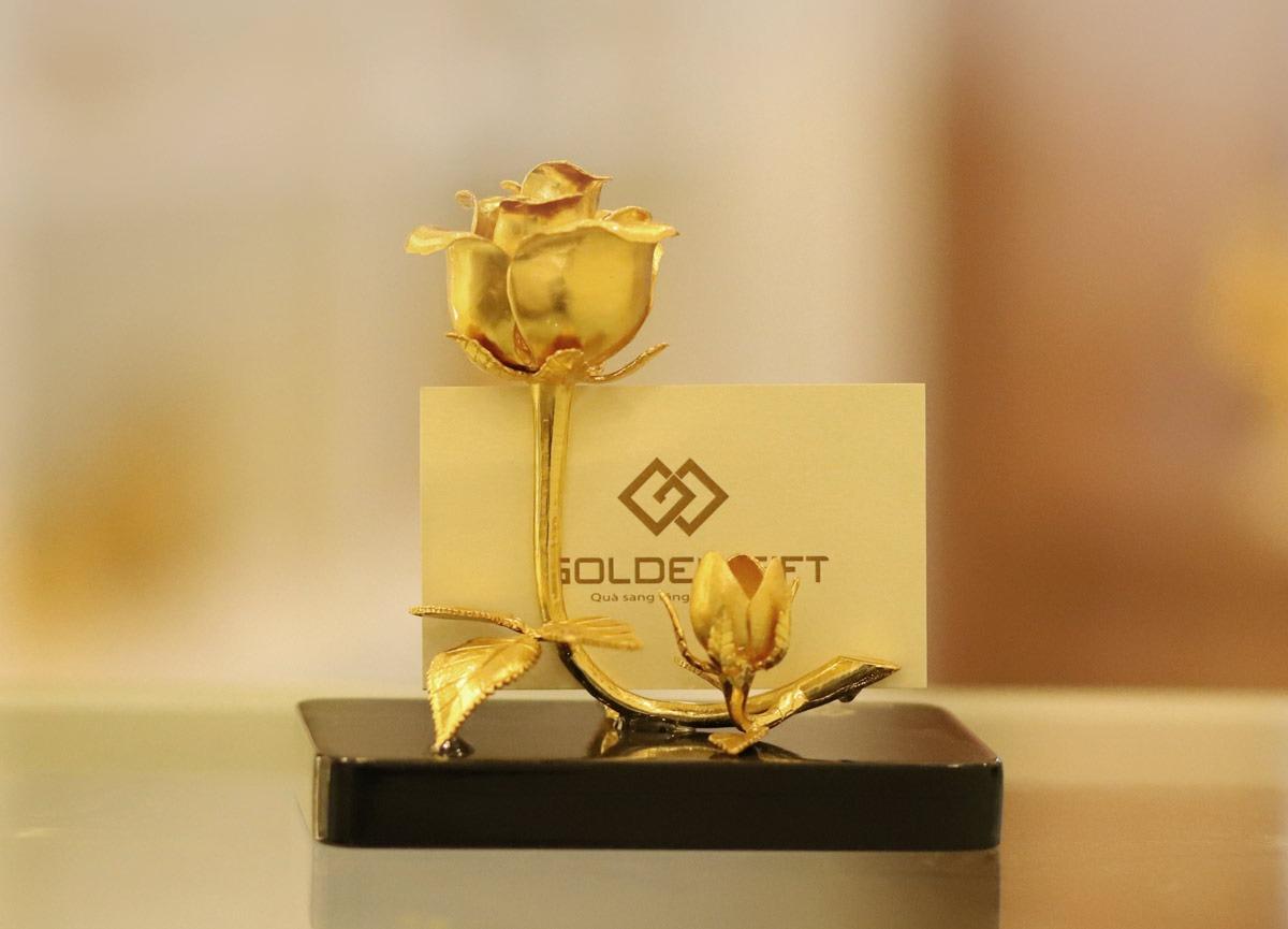 Bông hồng mạ vàng Golden Gift có thể dùng làm quà biếu nhân các dịp đặc biệt hoặc chúc thọ, sinh nhật người thân. Sản phẩm có thể làm đồ trang trí, trưng bày trên bàn làm việc, phòng khách. Bông hồng gồm cành và lá được gia công tỉ mỉ kèm đế màu đen bên dưới. Sản phẩm có giá giảm 29% còn 2,125 triệu đồng (giá gốc 3 triệu đồng).