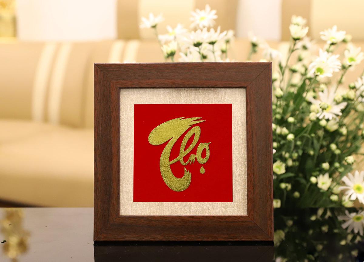 Tranh chữ Thọ thư pháp mạ vàng 24K để bàn là một trong những món quà ý nghĩa, được nhiều người dùng làm quà chúc thọ bố mẹ, ông bà. Sản phẩm có giá 1,7 triệu đồng, giảm 32% so với giá gốc. Khung tranh vuông với cạnh 20 cm, có đế đỡ phía sau.