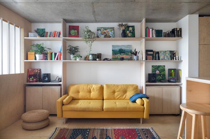 Khu vực bếp nấu không thể nhìn thấy từ phòng khách mà khuất sau quầy bar ở giữa phòng. Phòng khách, bếp ngăn cách với phòng ngủ bằng vách ngăn ván ép nhẹ. Đồ nội thất đến từ các vật liệu như gỗ, được phủ sơn tự nhiên.  Chủ nhà đã lấp đầy căn hộ bởi những bức tranh, đồ trang trí và nhiều cây trồng. Trong phòng khách còn có một tấm thảm từ Morocco.