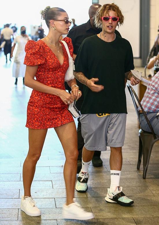 Hailey khoe dáng gợi cảm trong bộ đầm hoa mini, tay phồng và khoét sâu phần cổ. Justin mặc theo phong cách thoải mái với áo phông và quần short từ dòng thời trang Drew của anh.