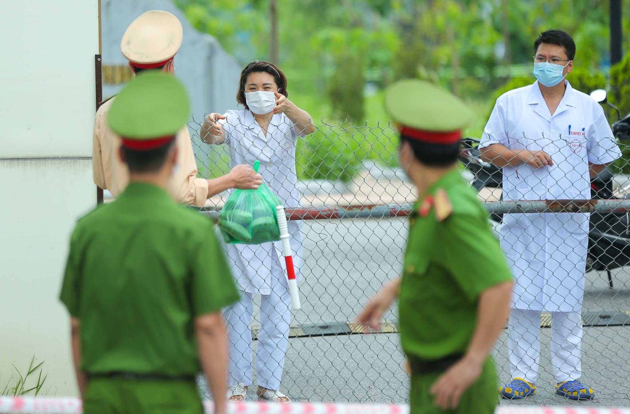 Các bác sĩ tại Bệnh viện Nhiệt đới Trung ương nhận tiếp tế sau lệnh phong toả. Ảnh: Anh Hùng.