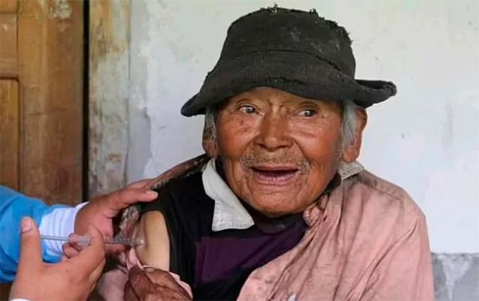 Cụ ông tự nhận sinh năm 1900 được tiêm mũi vaccine Covid-19 đầu tiên. Ảnh: Newsflash.