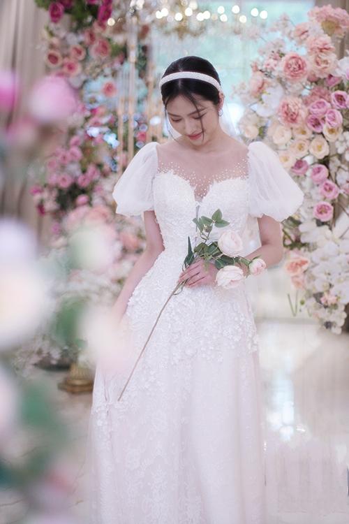 Hoạ tiết ren hoa được đắp bất đối xứng để tạo điểm nhấn. Cổ illusion cho phép đính kết hạt tạo thành dải hạt lấp lánh, tạo điểm nhấn cho trang phục.