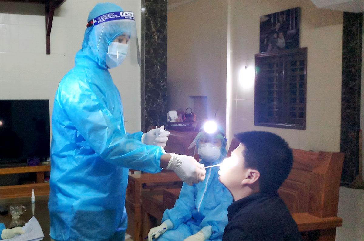 Lực lượng chức năng lấy mẫu xét nghiệm nCoV đối với những người liên quan nữ bệnh nhân 32 tuổi ở thôn Việt Yên, xã Việt Tiến, khuya 5/5. Ảnh: Hùng Lê