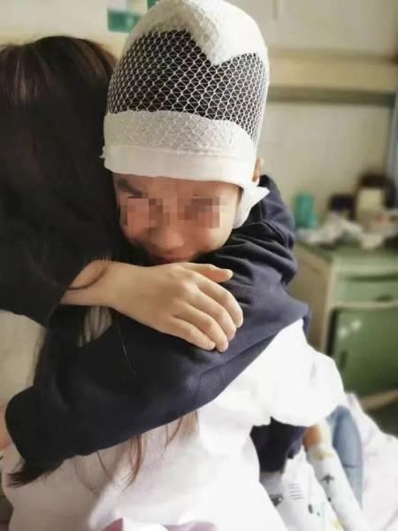 Cậu bé khóc lóc, sợ hãi ôm chặt mẹ khi ở bệnh viện. Ảnh: SCMP.