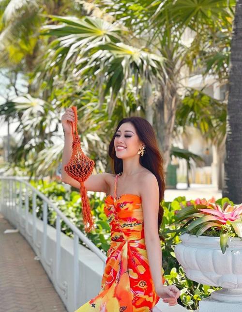 Diện đầm cúp ngực in họa tiết cam - đỏ rực rỡ, Khánh Vân mix thêm phụ kiện túi dây đan, thắt nút theo đúng trào lưu thịnh hành.