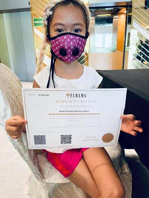 Con gái Đoan Trang cầm chứng nhận hoàn thành thời gian cách ly theo quy định.