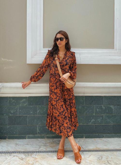 Đầm nâu đậm, nâu sòng dễ khiến phái đẹp già hơn tuổi, do đó Tăng Thanh Hà khéo chọn váy hoa để phối đồ đồng điệu với túi đep chéo và dép da mùa hè.