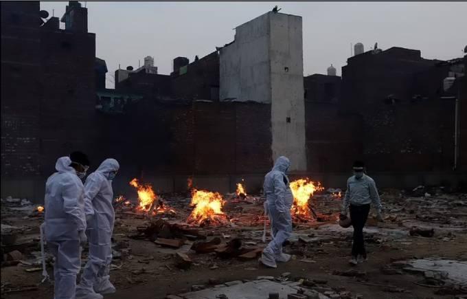 Người thân các nạn nhân Covid-19 thực hiện những nghi lễ cuối cùng trong một lễ hỏa táng tại nhà hỏa thiêu ở Delhi hôm 10/5. Ảnh: Anadolu Agency.