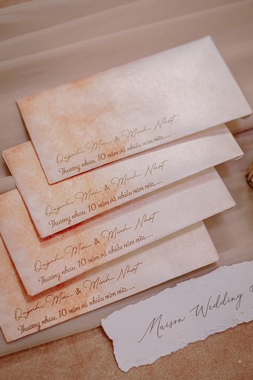 Bộ thiệp mời được cô dâu lên thiết kế riêng với chữ calligraphy, mang sắc màu cam ombre, nhắc về chặng đường 10 năm đã qua và những năm kế tiếp.