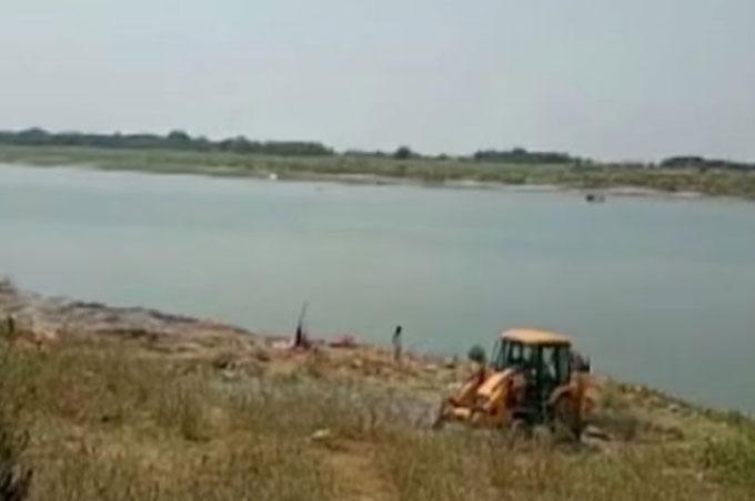 Một chiếc xe máy xúc đậu bên bờ sông Hằng - đoạn phát hiện các thi thể trôi dạt vào bờ hôm 11/5. Ảnh: timesnownews.