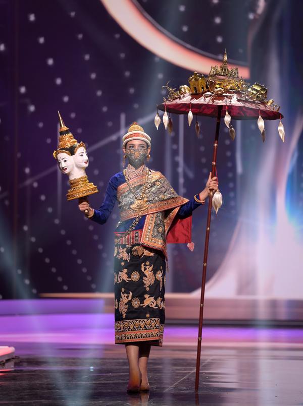 Người đẹp Lào, Christina Lasasimma, duyên dáng trong bộ trang phục truyền thống và cầm theo chiếc ô đính mô hình những ngôi chùa vàng.