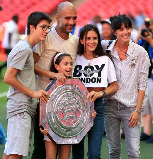 Vợ chồng HLV Pep Guardiola bên các con mừng vô địch Siêu Cup Anh Community Shield của Man City năm 2018. Trong ảnh Maria đứng giữa bố mẹ. Ảnh: PA.
