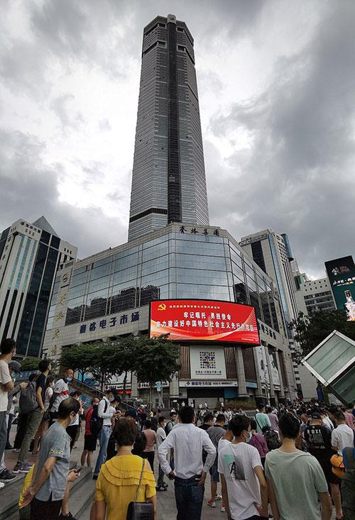 Người dân đứng tụ tập trước toà SEG Plaza ở Thâm Quyến sau khi nó ngừng rung lắc chiều 18/5. Ảnh: Weibo.