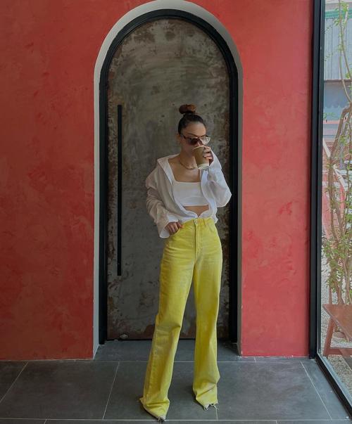 Gam trắng được xem là người bạn của mọi sắc màu vì thế nó đễ dàng phối hợp cùng tông nóng - lạnh một cách linh hoạt. Yến Trang giúp mình nổi bật khi đi cafe với trang phục sơ mi, áo hở eo và quần denim tông vàng chanh.