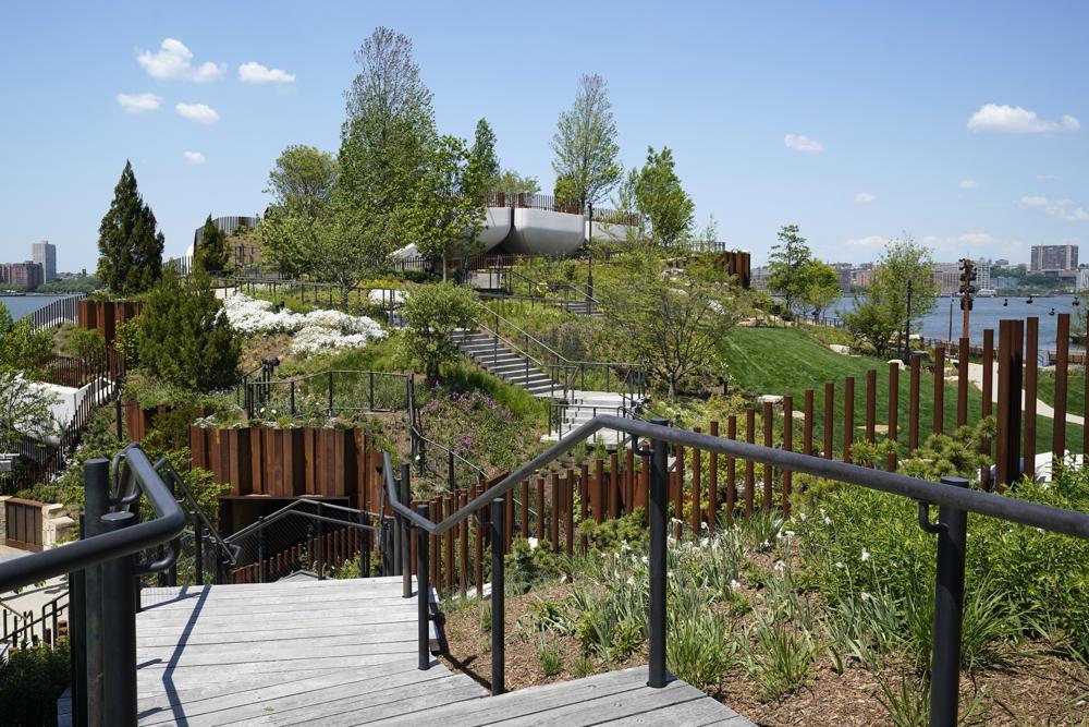 Cầu thang lát gỗ dẫn đến một trong những điểm cao nhất của Little Islad, nơi có nhiều cây xanh tươi mát. Tại đây chăm sóc hơn 350 loại hoa và các loại cây bụi, cây lớn. Ông trùm truyền thông kiêm nhà từ thiện tỷ phú Barry Diller chụp ảnh hôm thứ Ba, ngày 18 tháng 5 năm 2021, tại Đảo Bé, một công viên công cộng mới dọc theo sông Hudson ở New York. Diller, hợp tác với Hudson River Park Trust, đã tìm cách sửa chữa và sử dụng lại Cầu tàu 54, bị hư hại bởi Superstorm Sandy vào năm 2012. Ông đã tưởng tượng ra một không gian công cộng kết hợp giữa thiên nhiên và nghệ thuật và tạo ra một ốc đảo tại địa điểm này. Điều tôi nghĩ trong đầu là xây dựng một thứ gì đó cho người dân New York và cho bất kỳ ai ghé thăm — một không gian mà ngay từ cái nhìn đầu tiên đã thấy chói mắt và khi sử dụng sẽ khiến mọi người hài lòng, Diller nói.Một cầu thang dẫn đến một trong những điểm cao nhất của Đảo Bé, Công viên Sông Hudson mới, vào Thứ Ba, ngày 18 tháng 5 năm 2021, ở New York. Được thiết kế để tạo ra một trải nghiệm nhập vai kết hợp giữa thiên nhiên và nghệ thuật, công viên dự kiến sẽ mở cửa cho công chúng vào thứ Sáu. Có hai nhà hát, một không gian ăn uống bình dị ngoài trời, lối đi bộ quanh co và cầu thang dẫn đến nhiều tầm nhìn ra thành phố và một sân chơi.