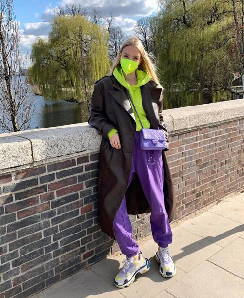 Leonie Hanne sử dụng áo hoodie màu chóe để tạo điểm nhấn khi diện quần thể thao và áo măng tô tông trầm.