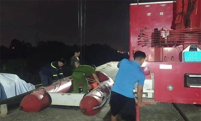 Nhà chức trách đưa xuồng tìm kiếm thi thể anh Tân dưới sông Lam, tối 24/5. Ảnh: Hùng Lê