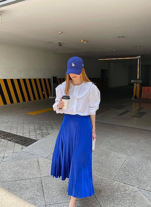 Áo cổ sen mang dáng dấp của phong cách classic kết hợp cùng chân váy midi, mũ lưỡi trai, giày thể thao sẽ mang tới sự thú vị cho set đồ street style mùa hè.