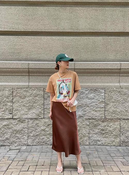 Set đồ đơn giản và phù hợp với những ngày nắng với cách mix áo thun in hoạ tiết cùng chân váy lụa, sandal cao gót và túi mini tiệp màu.