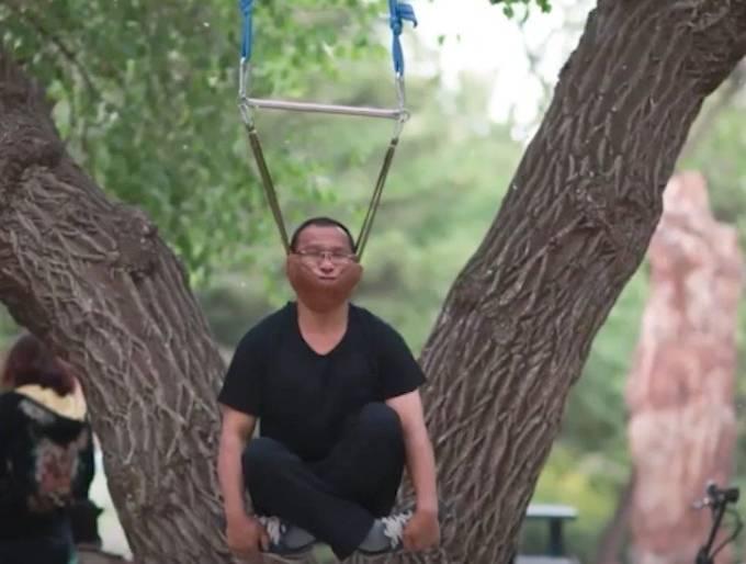 Một người đàn ông đặt cằm lên đại và đu mình lên cây nhằm chữa các bệnh về đốt sống cổ và lưng. Ảnh: O.C.
