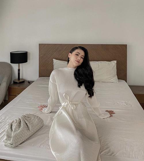 Phương Khánh khoe dáng trong phòng ngủ và lên kế hoạch làm việc tại nhà. Ngoài các mẫu váy suông tiện lời thì hoa hậu vẫn thể hiện sự đỏm dáng với trang phục dập ly nhuyễn. Phụ kiện đi kèm là túi da đan của Bottega.