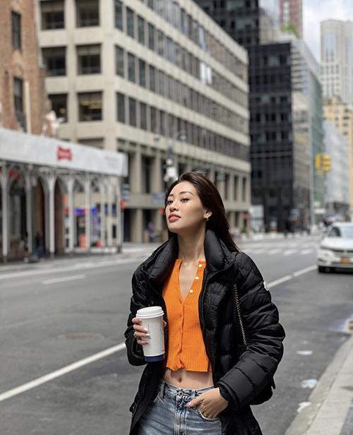 Áo dệt kim dáng hở eo được Khánh Vân chọn làm điểm nhấn cho set đồ giữ ấm gồm áo phao đen và quần jeans ống suông kiểu basic.