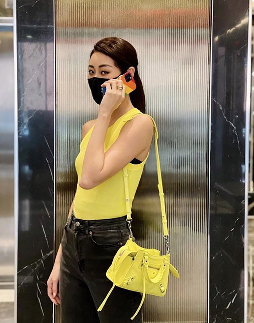 Khánh Vân chọn cách mix đồ ton-sur-ton với gam vàng - đen ăn ý trên set đồ gồm áo sát nách, quần jeans ống skinny và túi đeo chéo của Balenciaga.