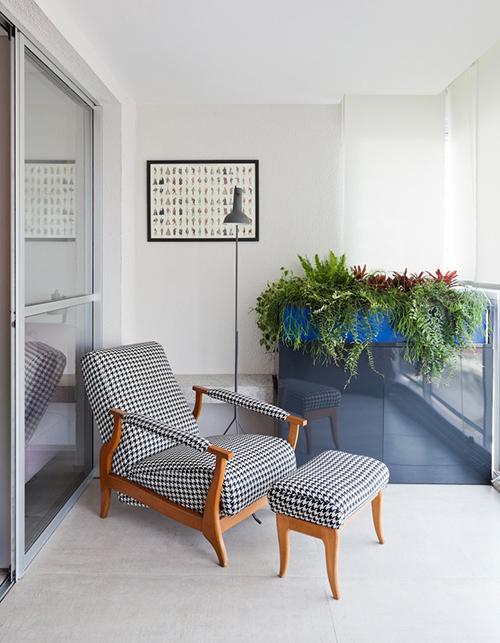 Phía bên ngoài ban công là ghế và đôn gỗ để chủ nhà đọc sách, thư giãn. Không gian được tạo điểm nhấn với cây xanh.