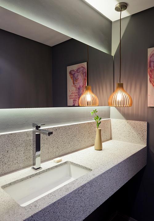 Phòng vệ sinh của căn hộ mang tông xám nhưng có thêm đèn vàng tạo sự ấm áp.