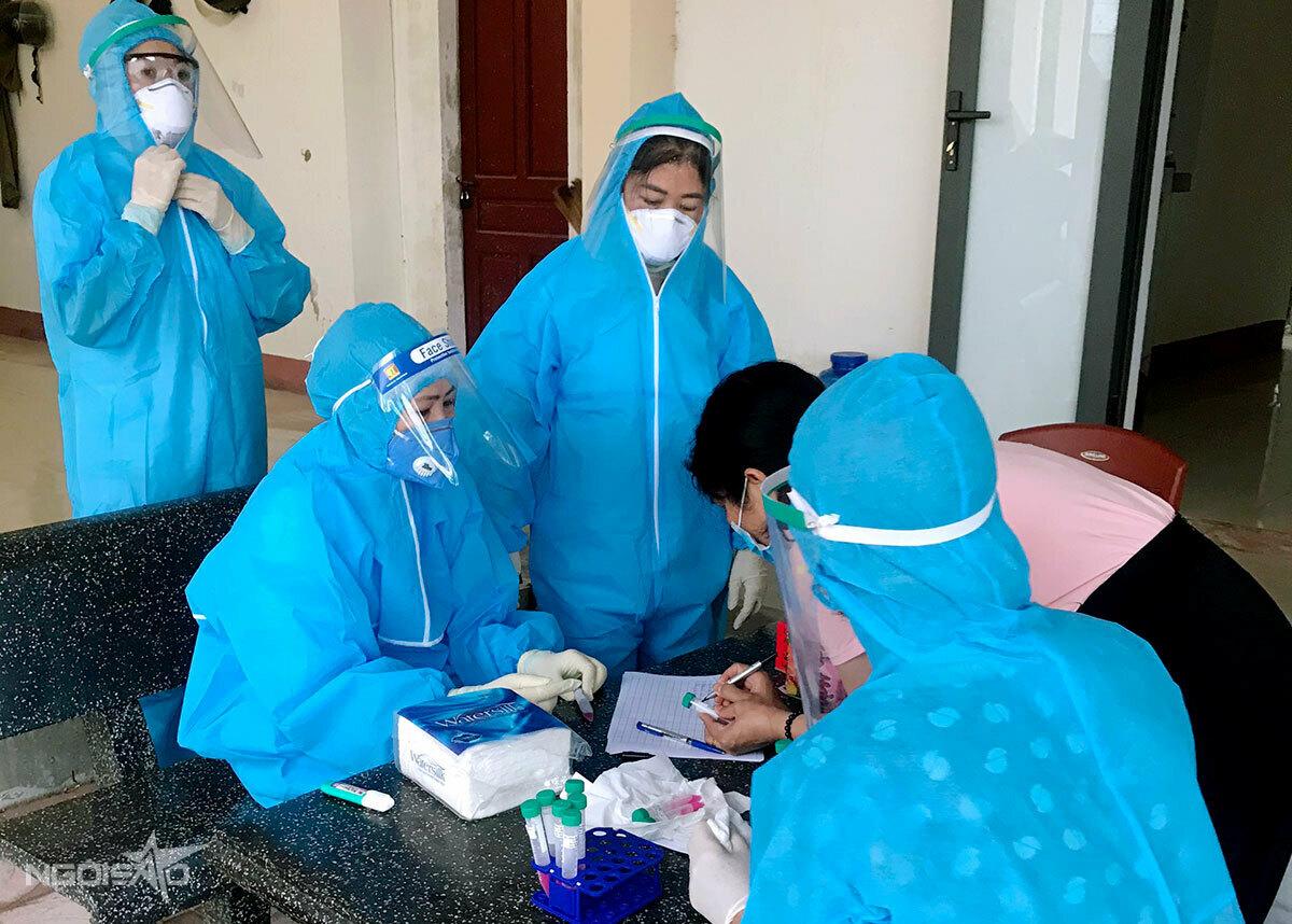 Cán bộ y tế lấy mẫu xét nghiệm cho người dân vùng dịch TP Hà Tĩnh. Ảnh: Hùng Lê