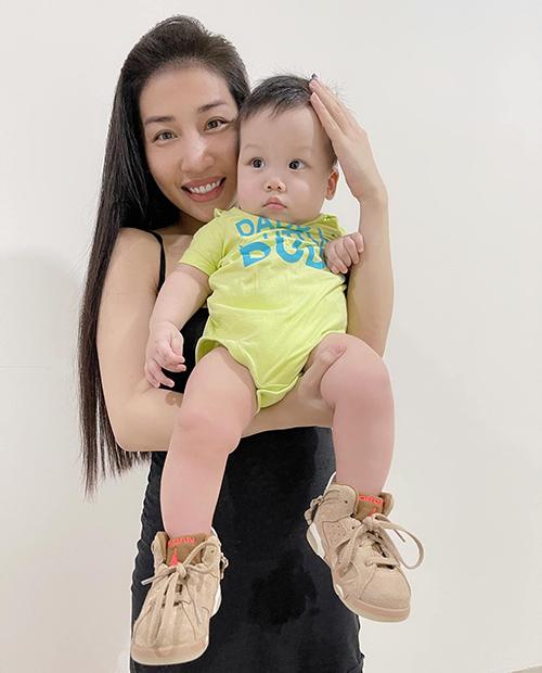 Bé Jin Quân, 8 tháng tuổi bên mẹ. Đôi giày em diện là do ba mua gửi về Việt Nam.