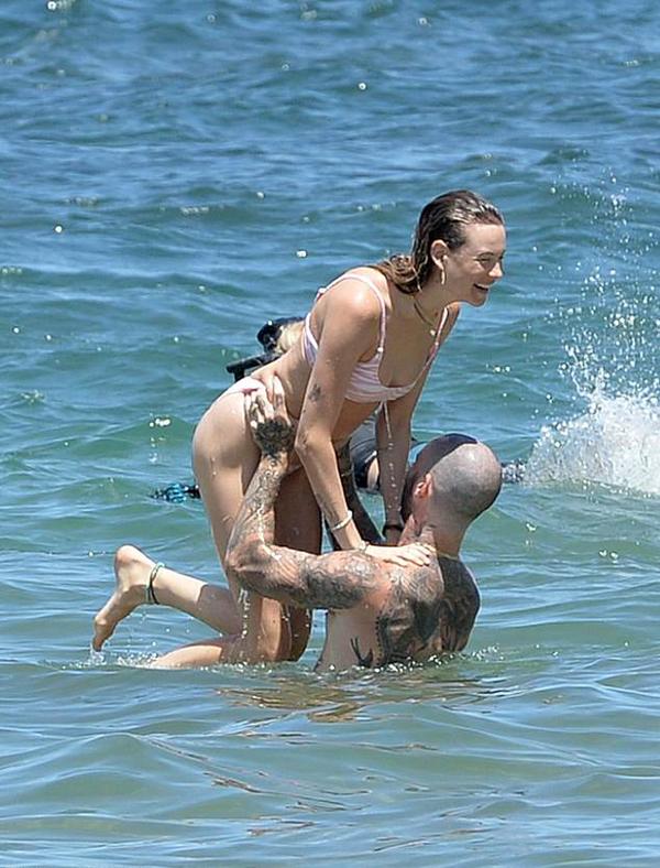 Adam Levine và bà xã kém 10 tuổi quấn quýt trên bãi biển Maui. Nam ca sĩ nâng bổng vợ với hai cánh tay cơ bắp cuồn cuộn khiến cô bất ngờ thích thú.