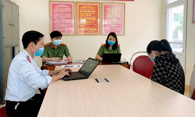 Người phụ nữ (ngoài cùng, góc phải) làm việc với nhà chức trách. Ảnh: Hùng Lê