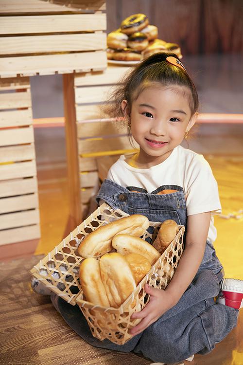 Bé Celine Nguyễn với hình ảnh trong trẻo bên đạo cụ của buổi chụp ảnh là những chiếc bánh mì.
