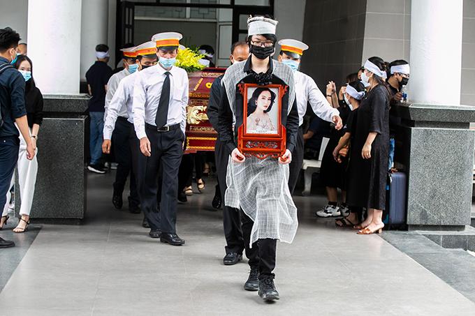 Con trai Duy Anh đỡ di ảnh Thu Thuỷ tại nhà tang lễ. Ảnh: Đình Tùng