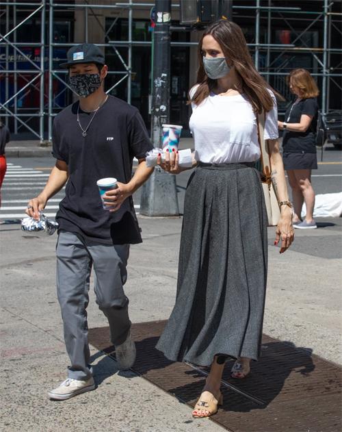 Nữ diễn viên và các con lót dạ bằng đồ ăn nhanh giữa buổi dạo chơi ở New York. Jolie lựa chọn trang phục đơn giản, thoáng mát và xỏ sandal đế bằng để thuận tiện cho việc đi bộ.