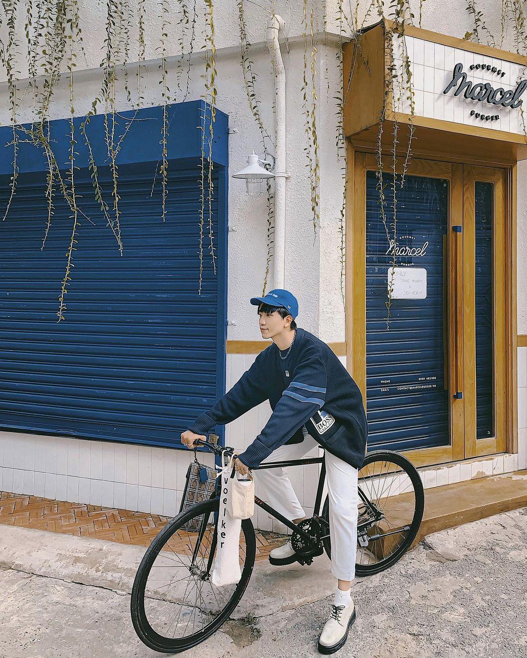 Stylist Monsimi gợi ý phái mạnh dạo phố với áo cardigan dáng rộng, kết hợp mũ lưỡi trai, áo crewneck và quần relax fit màu trắng.
