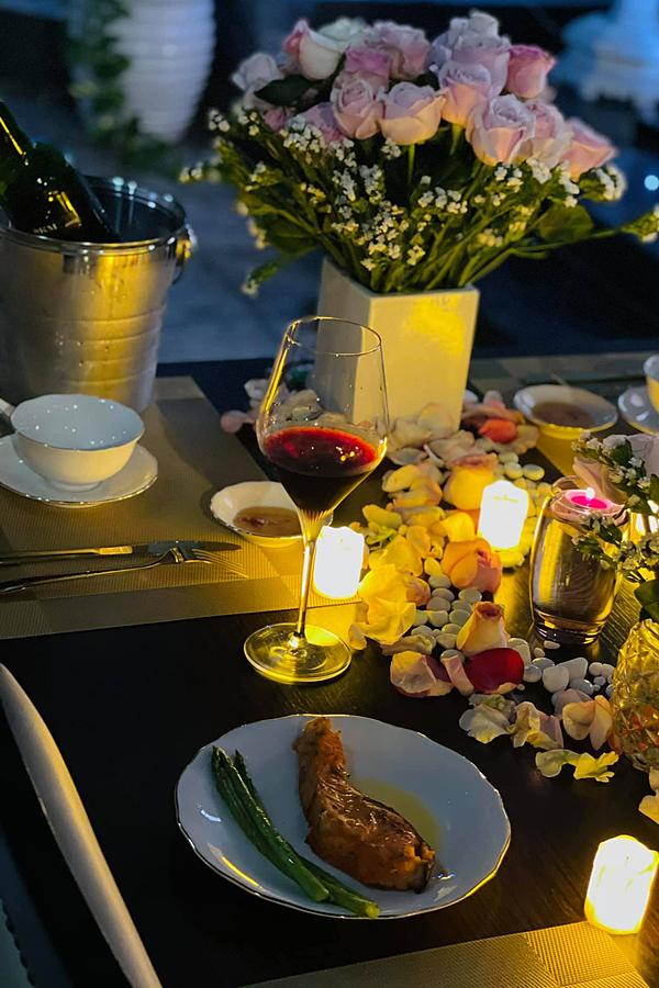 Buổi sinh nhật diễn ra trong không gian ấm cúng tại nhà. Bàn ăn được trình bày theo phong cách phương Tây với những bình hoa hồng rực rỡ, nến thơm lung linh. Cô bật mí mình trang trí thêm những bộ chén, dĩa để bàn ăn đỡ trống trải.