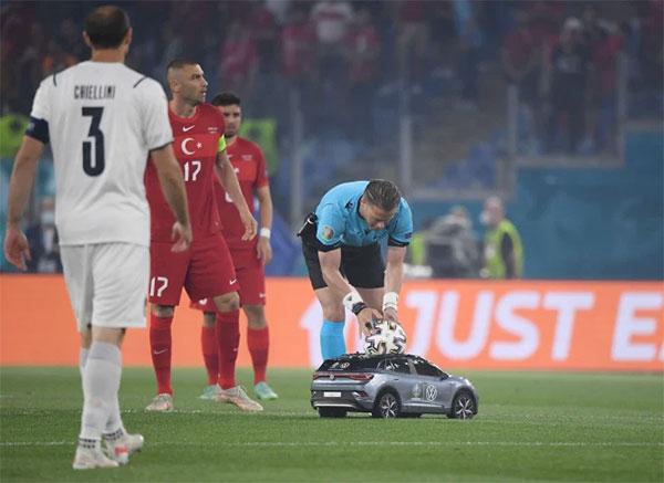 Trọng tài nhấc trái bóng từ chiếc ôtô điều khiển từ xa trước khi đưa cho cầu thủ Thổ Nhĩ Kỳ giao bóng. Ảnh: Reuters.